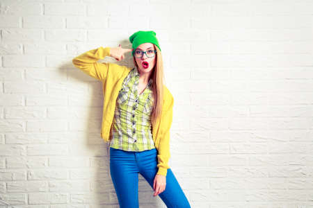 Funny Hipster Girl at White Brick Wall Background. Street Syle Teenage Going Crazy. Circling a First Finger by Her Temple. Trendy Fashion Outfit in Spring or Autumn. Copy Space. photo