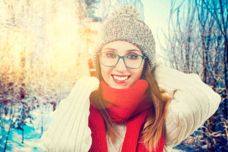 Happy Smiling Girl in Red Scarf, Sweater, Beanie Hat and Glasses in Snowy Park at Sunset. Fashion Woman in Winter Outdoors Concept. Backlit with Beautiful Bokeh. Toned Photo.
