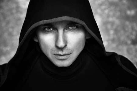 Mysterious Man in Black Hoodie. Sexy Hero Guy. Pastor or Wizard in Robe. Assassin or Witcher with Strong Face Expression in Cloak. Dark Magician Black and White Photo. Fantasy Book Cover Concept. Stock Photo