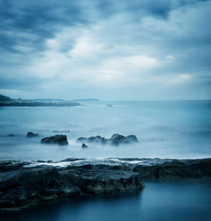 Peaceful Winter Seascape. Sea or Ocean with Dramatic Sky. Long Exposure. Calm Water and Moody Sky. Cold Mysterious Tranquility Concept. Blue Toned Photo with Copyspace. Banco de Imagens