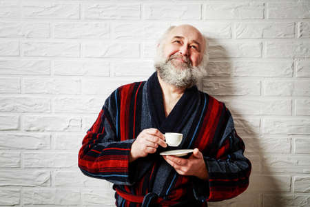 Portrait of Happy Senior Man with Beard in Vintage Bathrobe Drinking Coffee and Dreaming. Mature Old Man with Coffee Cup Relaxing and Looking Up. White Brick Wall Background. Copy Space.