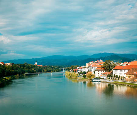 Maribor Old Town View and Drava River on Mountains Background. Popular Touristic Destination in Slovenia, Europe. Beautiful Slovenian Landscape. Copy Space.