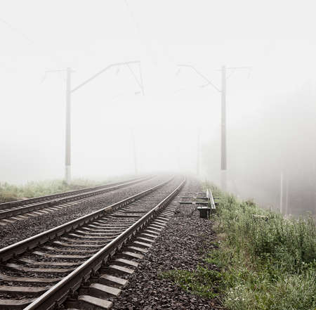 Railway in Fog. Misty Morning Landscape. Empty Railroad. Toned and Filtered Photo with Copy Space. Mystical Nature Background. Banco de Imagens