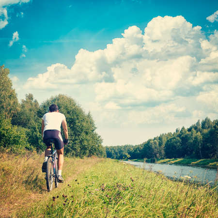 Rear View of a Man Riding a Bike on River Bank. Beautiful Nature Background. Healthy Lifestyle and Leisure Activity Concept. Toned and Filtered Instagram Styled Photo with Copy Space. Banco de Imagens