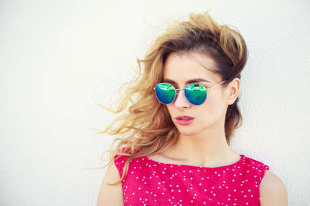 Portrait of Beautiful Fashion Woman in Sunglasses. Trendy Romantic Girl in Summer. Stylish Lovely Female. White Wall Background Copy Space. Not Isolated Toned Photo. Banco de Imagens