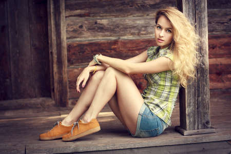 Trendy Hipster Teenage Girl Sitting and Looking at Camera. Beautiful Woman Outdoors. Street Style Fashion. Toned and Filtered Photo with Copy Space. Wooden Background.