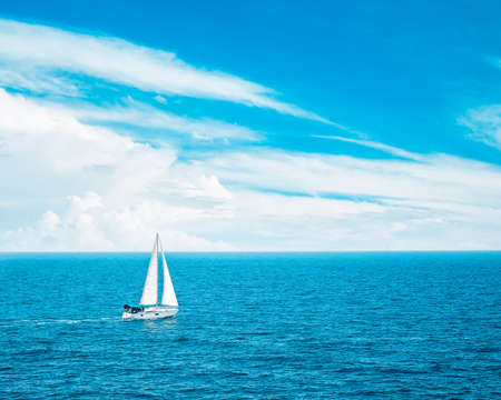 Beautiful Seascape with White Yacht Sailing in Blue Sea. Clouds on the Bakground. Toned Photo with Copyspace.