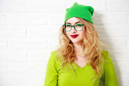 Portrait of Smiling Street Style Hipster Girl. Young Woman in Greenery Colors with Creative Makeup. Not Isolated Photo with Shadow. Trendy Casual Fashion Outfit. White Wall Background Copy Space.