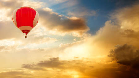 Red Hot Air Balloon Flying over Golden Sunset Sky. Amazing Evening Clouds Background. Toned Photo with Copy Space. Travel, Adventure and Freedom Concept. Banco de Imagens