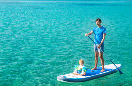 Young Father with His Son on SUP. Dad and Son Concept. Man and Boy Stand Up Paddling. Blue Sea Water. Floating Sup Board. Dad and Son on Summer Vacation Concept. Copy Space. Stock Photo