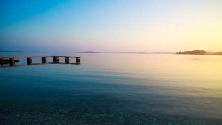 Calm Seascape in Warm Colors. Pier and Sea at Sunset in Summer. Relaxing Ocean Background in the Evening. Tranquiluty and Relax Concept. Copy Space.