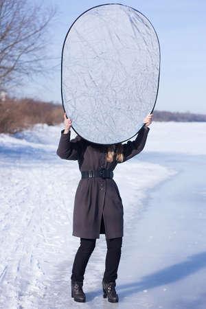 reflector: Photographer assistant holding reflector winter shoot lighting
