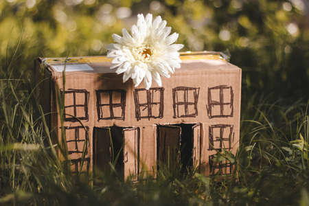 building loan: model of cardboard house with a bow of twine and key against green bokeh background. house building, loan, real estate or buying a new home concept.