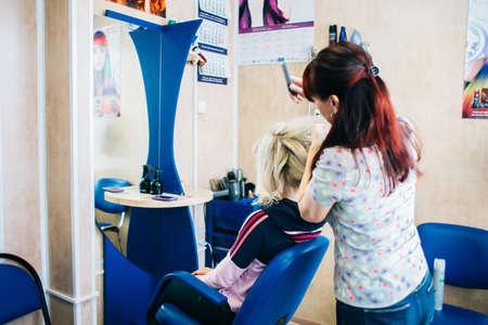 hair stylist: Hair stylist working on haircut for beautiful girl. Focus on the woman