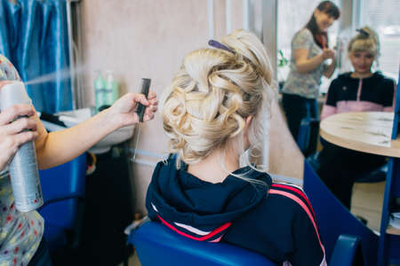 Hair stylist working on haircut for beautiful girl. Focus on the woman