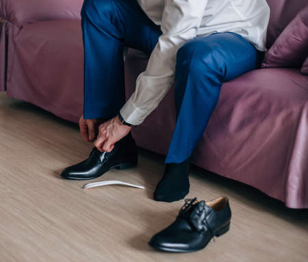 safety wear: Businessman or groom wears black shoes blue plants Stock Photo