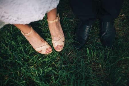 Füße von Braut und Bräutigam auf dem Rasen
