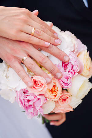 Hands and rings on wedding bouquet together Stock Photo - 65685635