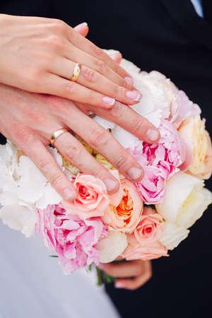 Mani e anelli su bouquet di nozze insieme Archivio Fotografico - 65685635