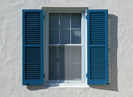 Open blue window shutters, against a white wall, in a hot country photo