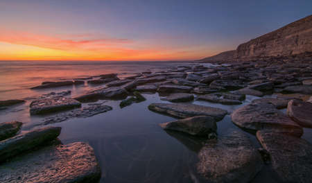 bathed: Spectacular sunset on a beach, with rocks in the foreground and a cliff bathed in the sunset
