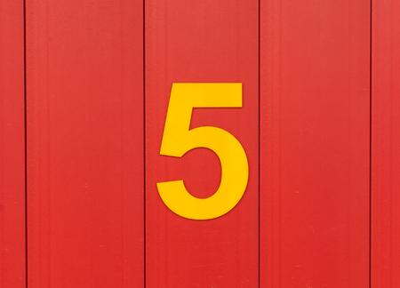 nombres: le nombre de cinq, jaune, mis contre le bois rouge vif