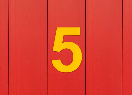 numbers: the number five, yellow, set against bright red wood Stock Photo