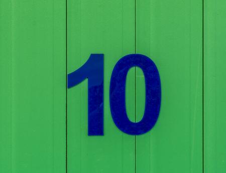 numero diez: el número diez, azul, en contraste con la madera de color verde brillante