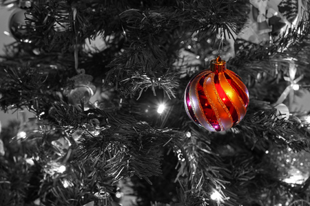 chirstmas: a single, isolated, red and gold striped Chirstmas bauble, against a black and white background