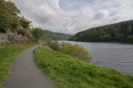 elan: Footpath alongside a picturesque lake, with wooded hills, in Wales, UK