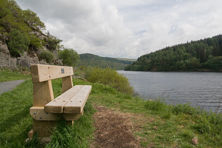 elan: Wooden bench beside a picturesque lake, in the Elan Valley, Wales, UK Stock Photo