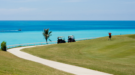 golfing: Golfing in the Sun, overlooking a tropical ocean Stock Photo