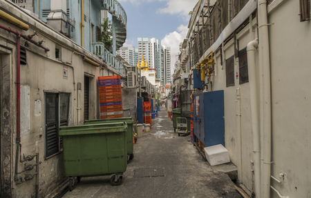 an ally: A Back Ally in Singapore. with stacks of crates and wheel bins Stock Photo