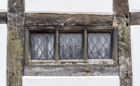 tudor: Traditional Tudor style window frame, with wooden beams surrounding the glass pane