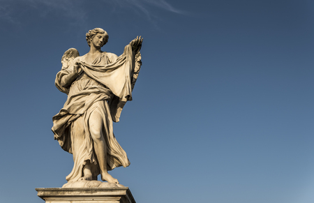 A large, stone statue of an angel, against a deep blue summer sky Stock Photo