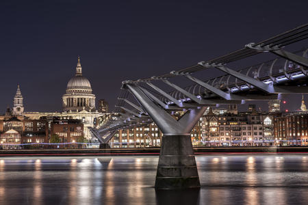 St Pauls Cathedral and the Millennium Bridge over the Thames, at night, with the lights shining on the opposite shore