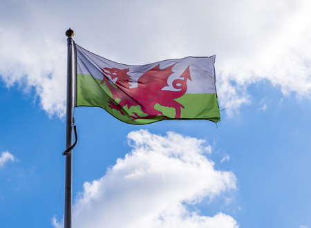 Welsh Flag flying in the wind, against a blue summers sky Stock Photo