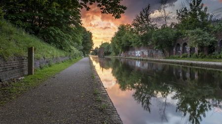 walk path: Sunset over the canal in Birmingham, UK, on a deserted footpath, with foliage flanking the tow path. The sun is creating a dramatic red and orange cloudscape in the sky