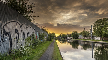 A graffiti covered wall, alongside a calm, flat canal, as the sun sets on a summers day.  the clouds and sky are reflecting in the still, flat water