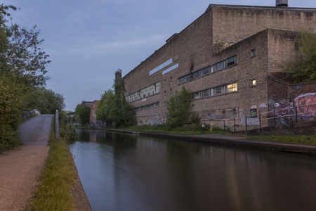 An old, industrial era warehouse, alongside the Birmingham canal, in the UK Stock Photo