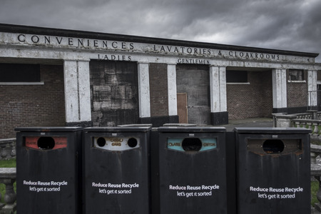 conveniences: An abandoned toilet block, decaying with age, with four recycling bins in the foreground, also in poor condition, located in Barry Island, Barry, Wales, UK