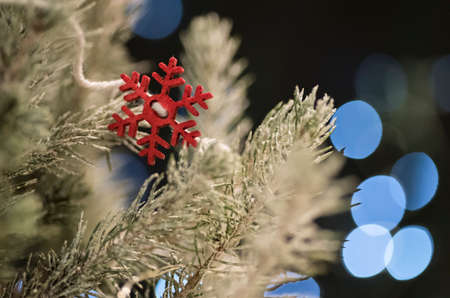 Detail of a red, wooden snowflake decorating an indoor Christmas tree