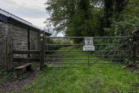田舎道の金属製の門で、「プライベート、釣りも駐車場もない」と書かれた看板が貼ってある