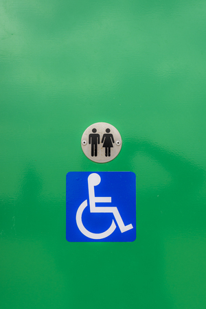 Disabled toilet sign, against a green background Stock Photo