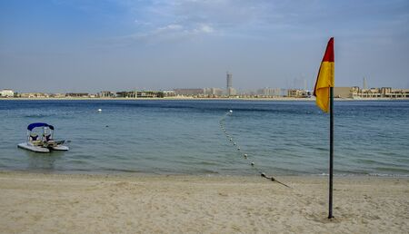 A safety flag, on the shore of a calm beach in Dubai, with a small sea vessel anchored near the shore, on a warm summers evening Banco de Imagens