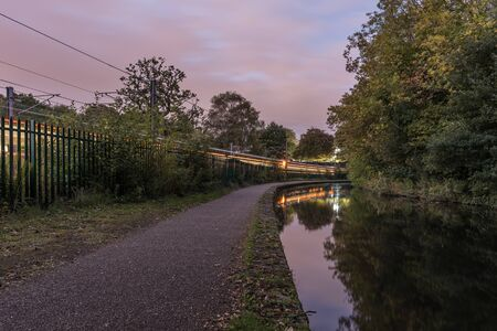 Worcester to Birmingham canal, in England, UK. The footpath by the side of the canal, with a train going past along side. The sky is beginning to darken as the sun goes down 写真素材