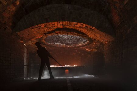 silhouette of iron worker stoking a furnace in the Blaenavon Iron Works, in Ebbw Vale, Wales
