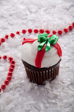 Christmas Chocolate Cup Cake With White Frosting and Green Bow Surrounded by Red Beads and Snow