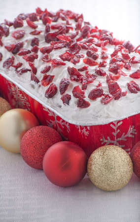 Christmas Bread With White Frosting and Cranberries Surrounded By Christmas Ornaments