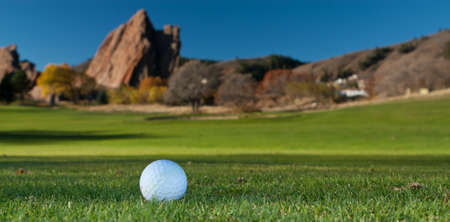 Golf Ball on the Green of a Golf Course With Large Red Rocks